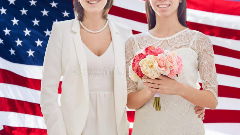 Close up of happy lesbian couple with flowers. People, homosexuality, same-sex marriage and love concept - close up of happy married lesbian couple with flower royalty free stock image
