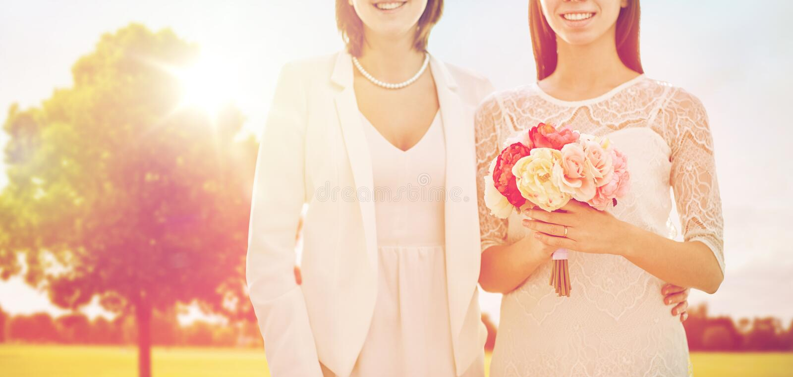 Close up of happy lesbian couple with flowers stock photo