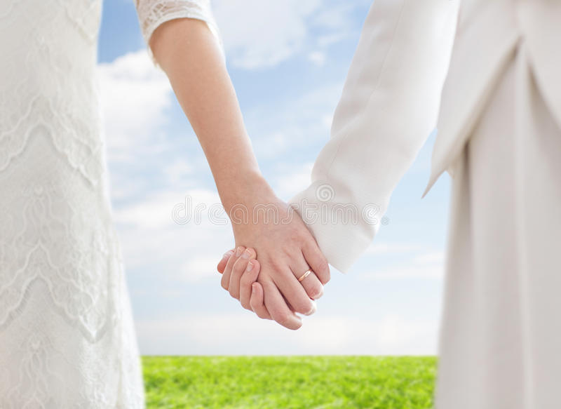 Close up of happy lesbian couple holding hands. People, homosexuality, same-sex marriage and love concept - close up of happy married lesbian couple holding royalty free stock photos