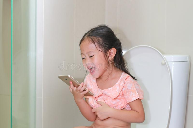Close-up happy little Asian child girl sitting on toilet and playing smartphone royalty free stock photos