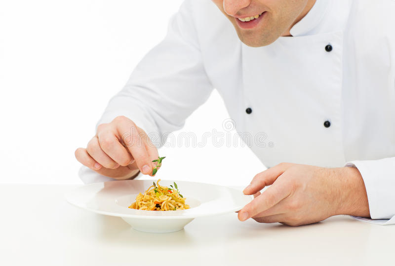 Close up of happy male chef cook decorating dish. Cooking, profession, haute cuisine, food and people concept - close up of happy male chef cook decorating dish stock images