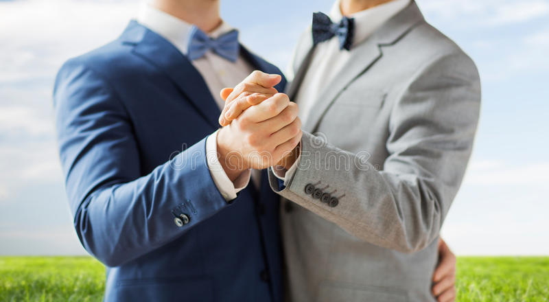 Close up of happy male gay couple dancing. People, homosexuality, same-sex marriage and love concept - close up of happy male gay couple holding hands and royalty free stock photography