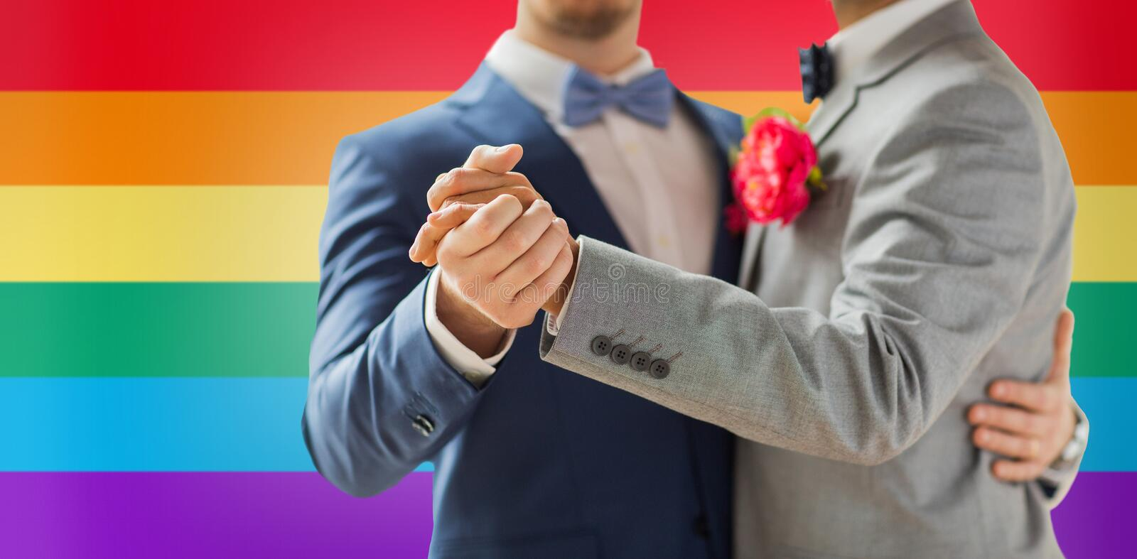 Close up of happy male gay couple dancing. People, homosexuality, same-sex marriage and love concept - close up of happy male gay couple holding hands and royalty free stock photo
