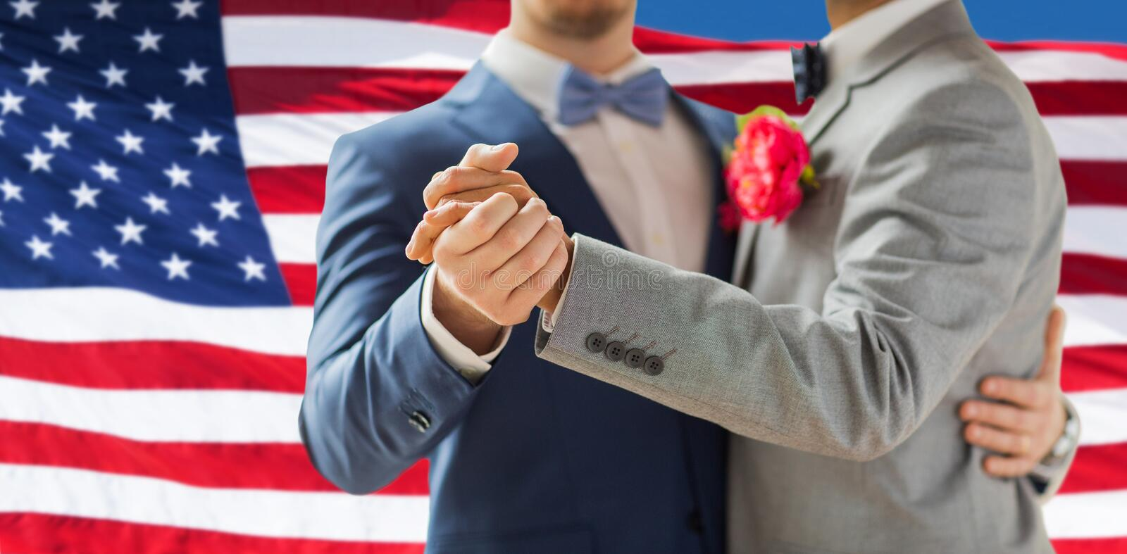 Close up of happy male gay couple dancing. People, homosexuality, same-sex marriage and love concept - close up of happy male gay couple holding hands and stock photo