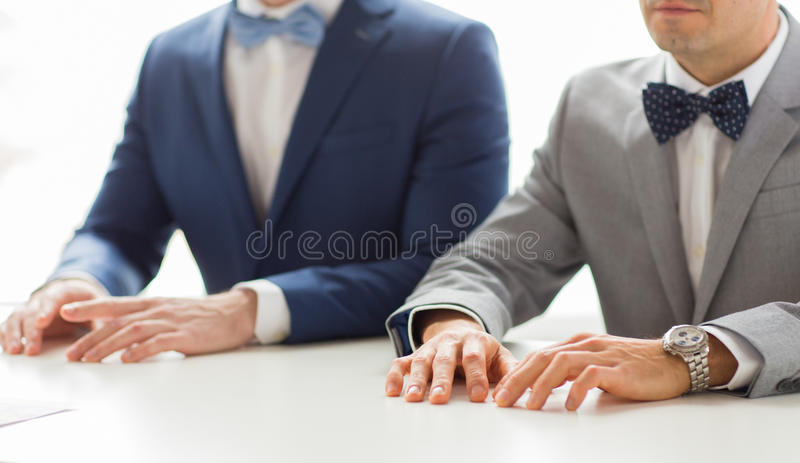 Close up of happy male gay couple hands on wedding. People, homosexuality, same-sex marriage and love concept - close up of happy male gay couple hands on royalty free stock image
