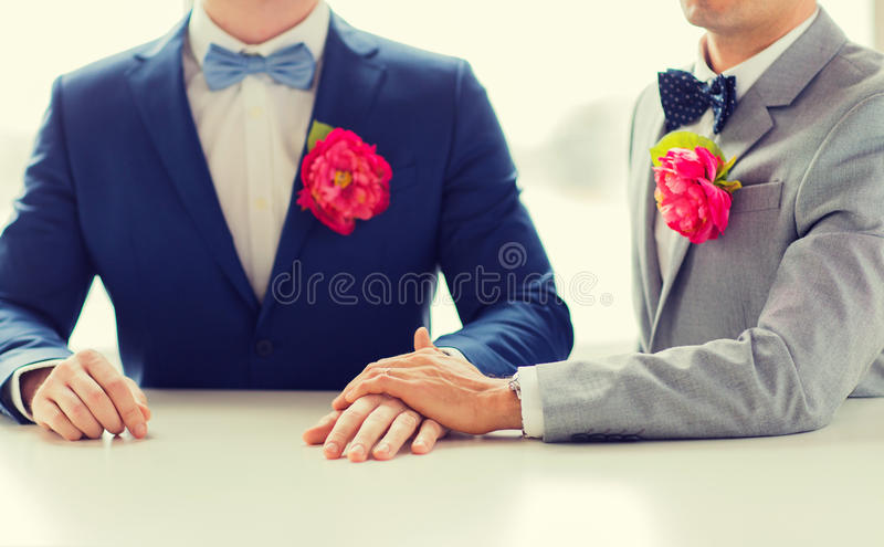 Close up of happy male gay couple holding hands. People, homosexuality, same-sex marriage and love concept - close up of happy married male gay couple in suits royalty free stock photography