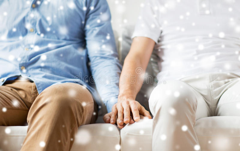 Close up of happy male gay couple holding hands. People, homosexuality, same-sex marriage, gay and love concept - close up of happy male gay couple holding hands stock photo