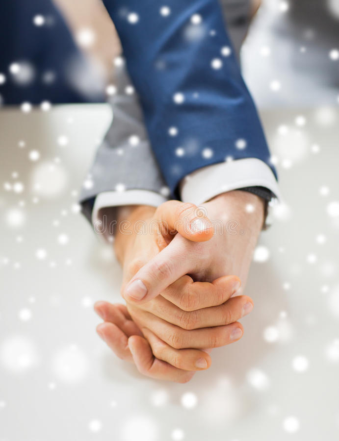 Close up of happy male gay couple holding hands. People, homosexuality, same-sex marriage and love concept - close up of happy male gay couple holding hands on royalty free stock photography