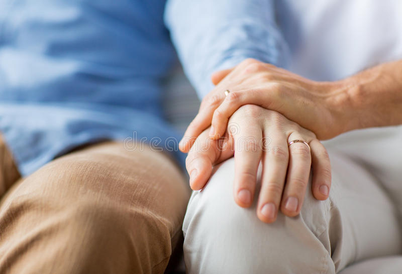 Close up of happy male gay couple holding hands. People, homosexuality, same-sex marriage, gay and love concept - close up of happy male gay couple holding hands stock image
