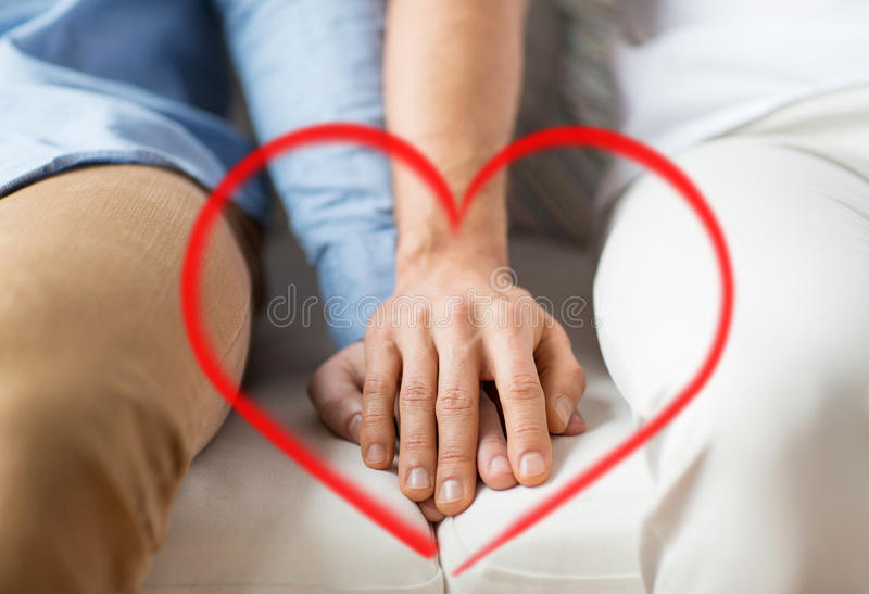 Close up of happy male gay couple holding hands. People, homosexuality, same-sex marriage, valentines day and love concept - close up of happy male gay couple royalty free stock image