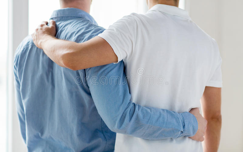 Close up of happy male gay couple hugging. People, homosexuality, same-sex marriage, gay and love concept - close up of happy male gay couple or friends hugging royalty free stock photos