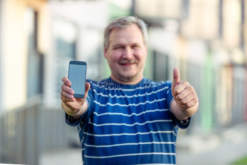 Close-up of happy man hand showing blank screen of smartphone on street. stock photo