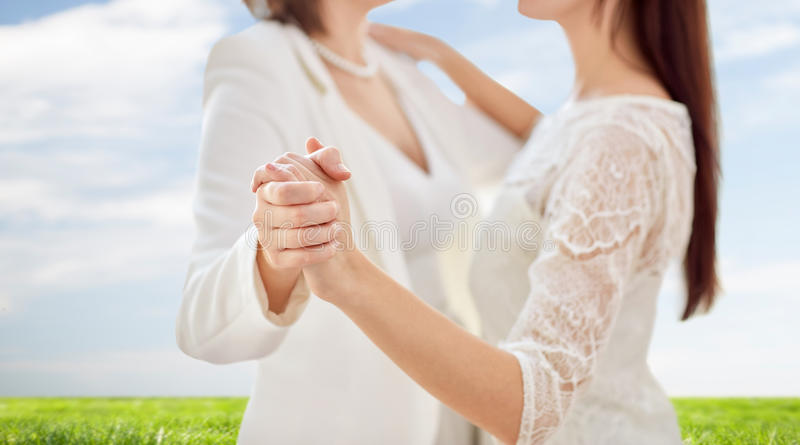 Close up of happy married lesbian couple dancing. People, homosexuality, same-sex marriage and love concept - close up of happy married lesbian couple dancing stock photo