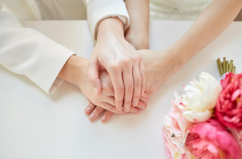 Close up of happy married lesbian couple hands. People, homosexuality, same-sex marriage and love concept - close up of happy married lesbian couple hands stock photography