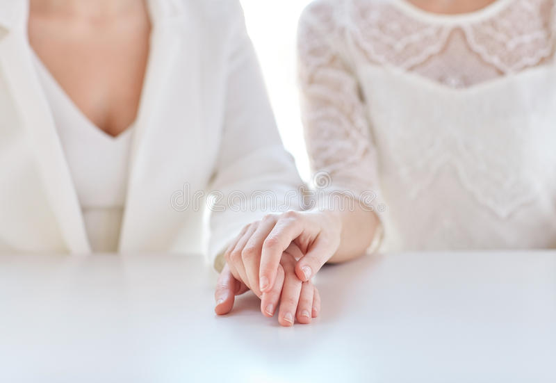 Close up of happy married lesbian couple hands. People, homosexuality, same-sex marriage and love concept - close up of happy married lesbian couple hands stock images