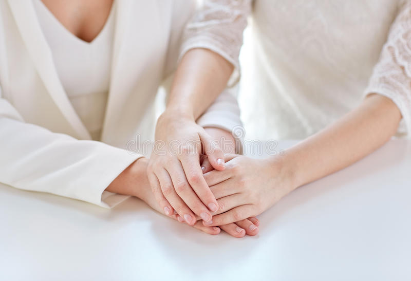 Close up of happy married lesbian couple hands. People, homosexuality, same-sex marriage and love concept - close up of happy married lesbian couple hands royalty free stock image