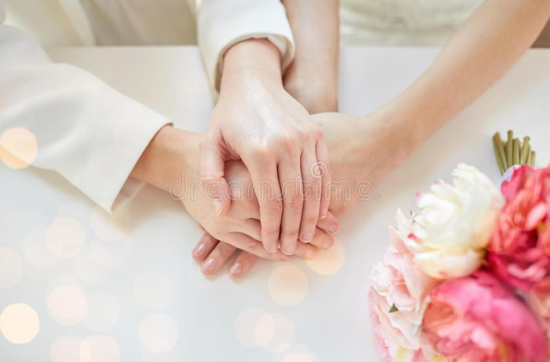 Close up of happy married lesbian couple hands. People, homosexuality, same-sex marriage and love concept - close up of happy married lesbian couple hands over royalty free stock images