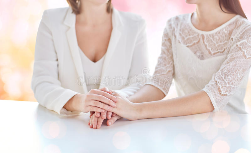 Close up of happy married lesbian couple hands. People, homosexuality, same-sex marriage and love concept - close up of happy married lesbian couple hands over royalty free stock image