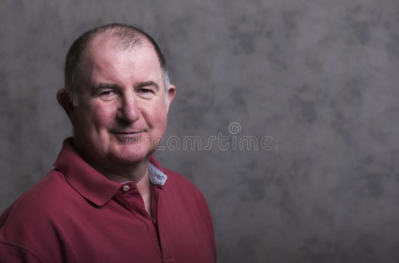 Close up of a happy mature man on a grey background. Taken with copy space stock photo