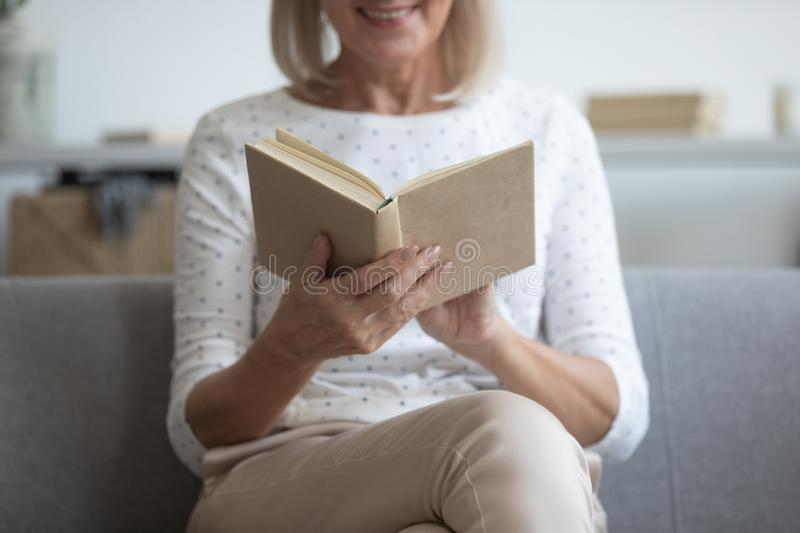 Close up of happy mature woman reading book at home stock photography