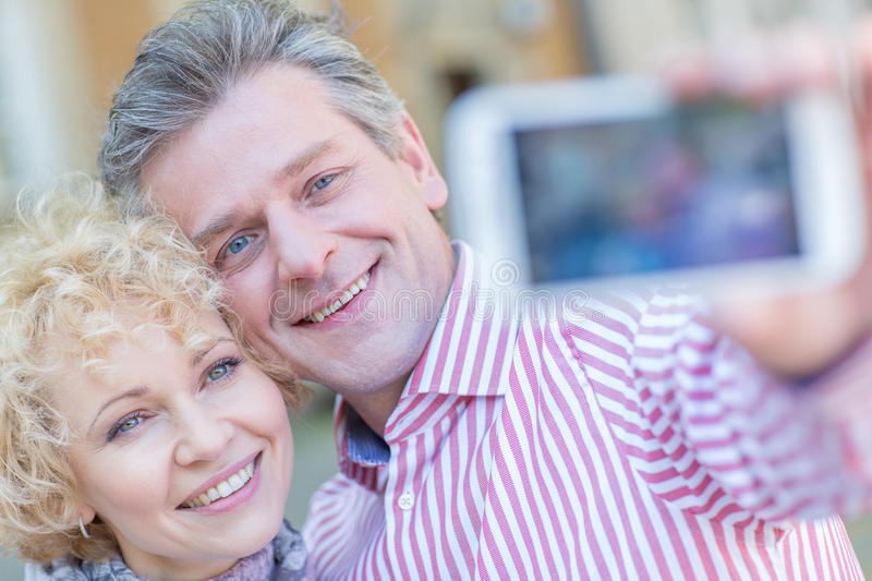 Close-up of happy middle-aged couple taking selfie through smart phone stock photos