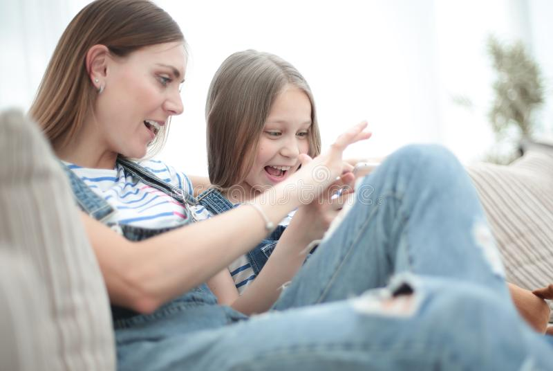 Close up.happy mom and her daughter are watching videos on smartphone royalty free stock photos
