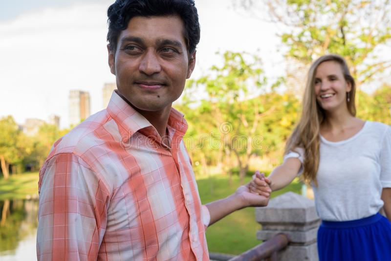Close up of happy multi ethnic couple smiling with Indian man le royalty free stock photo