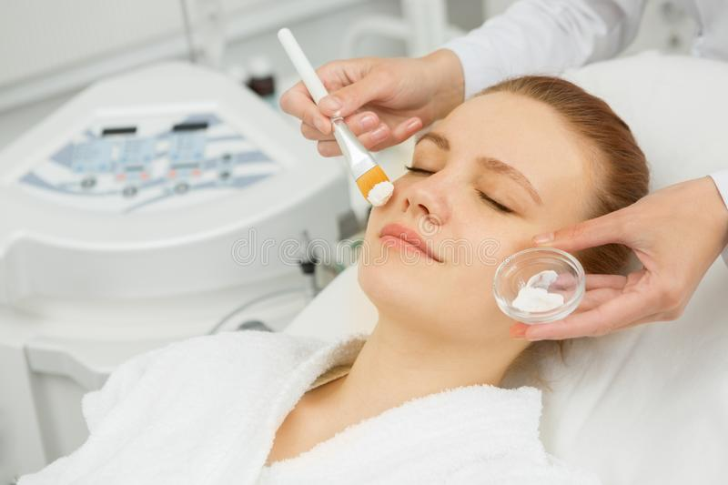 Attractive young woman getting facial mask at the spa stock photography