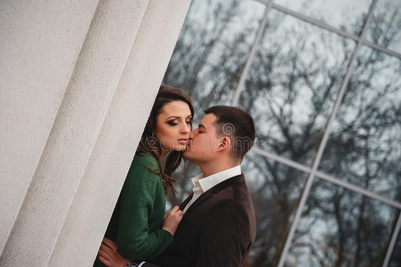 Close up of happy romantic attractive young couple kissing and hugging at the street royalty free stock images