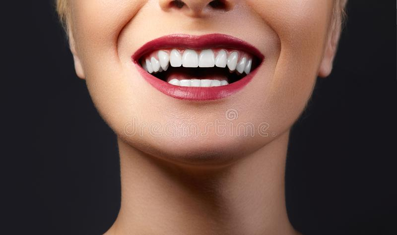 Close-up Happy Smile with Healthy White Teeth, Bright Red Lips Make-up. Cosmetology, Dentistry and Beauty care stock images