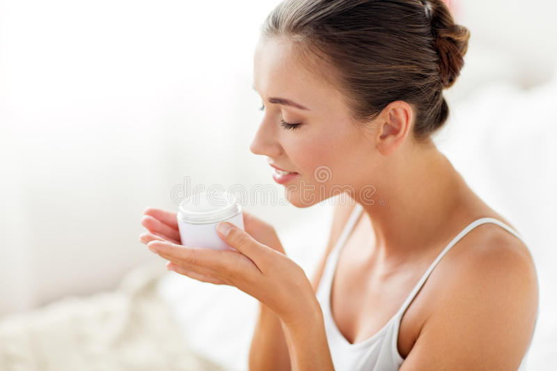 Close up of happy woman holding and smelling cream stock images