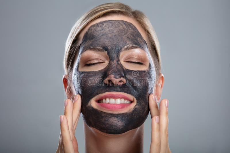 Happy Woman Using Activated Charcoal Face Mask royalty free stock images