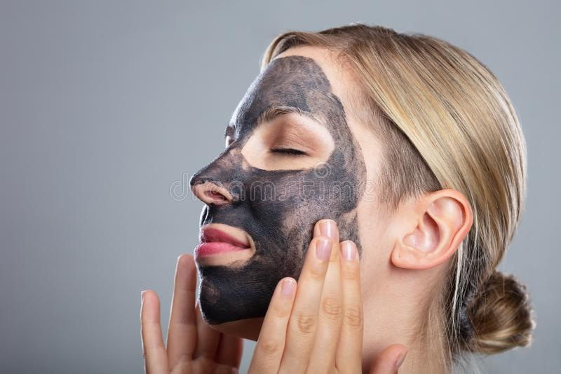 Happy Woman Using Activated Charcoal Face Mask royalty free stock image