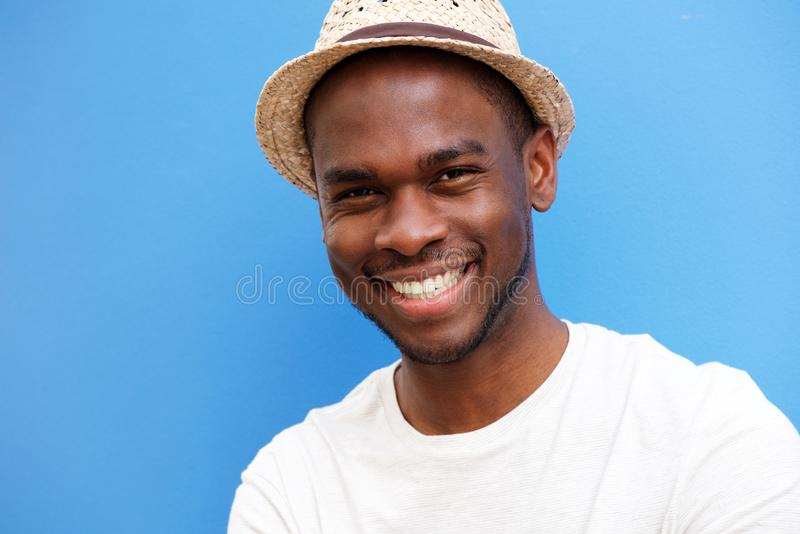 Close up happy young african american man with hat smiling against blue background stock photography