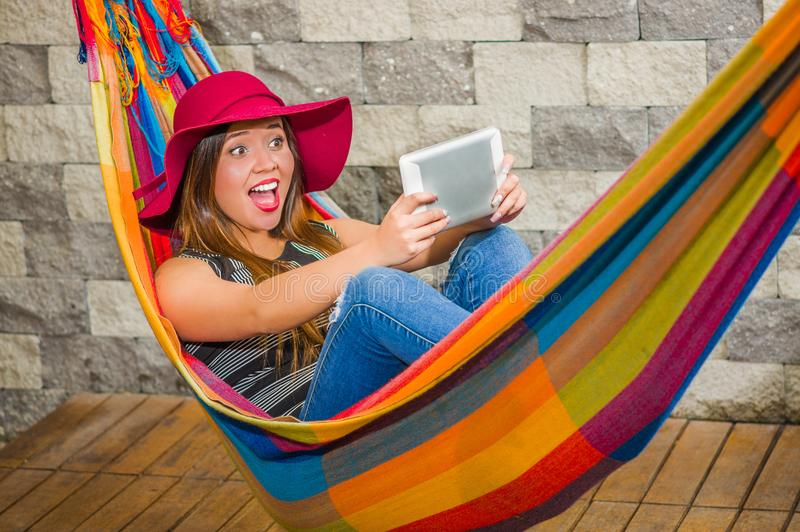 Close up of happy young beautiful woman wearing a red fashion hat and relaxing in a hammock and taking a selfie with her. Tablet, in blurred background royalty free stock photography