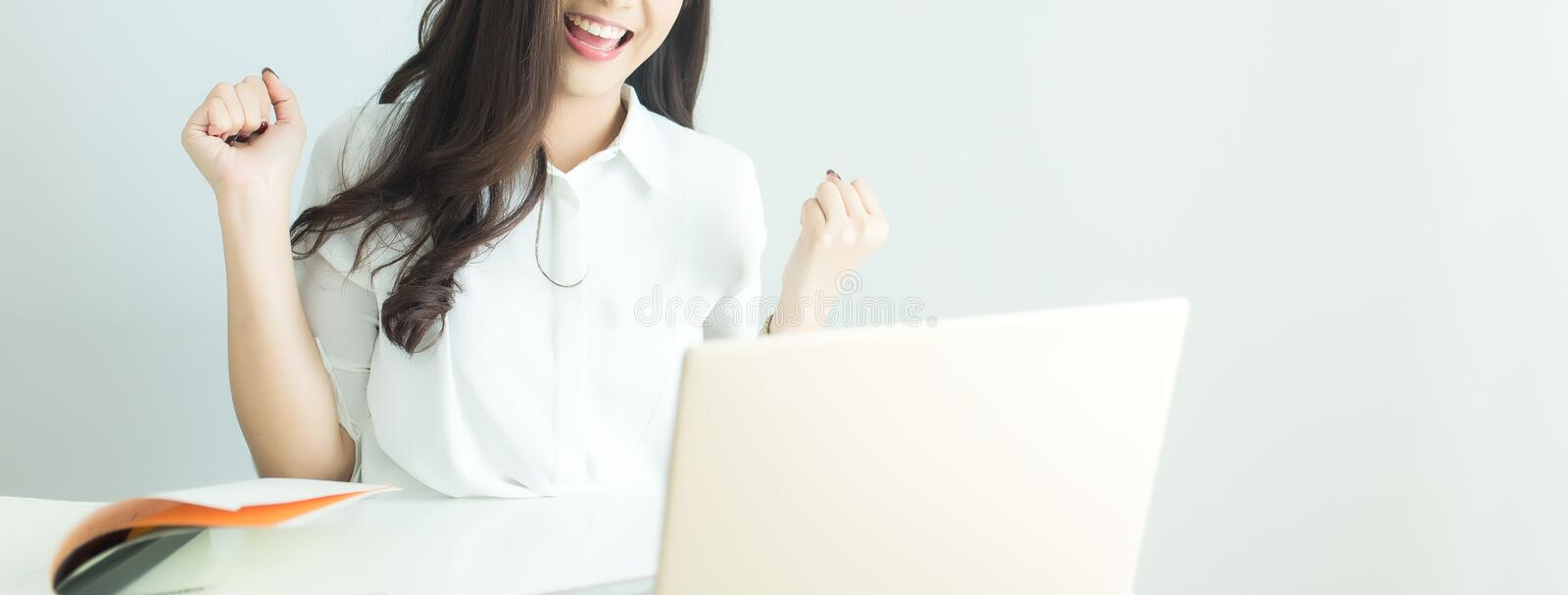 Close up of happy young business woman finished her work with laptop computer in modern office. Banner with copyspace stock image