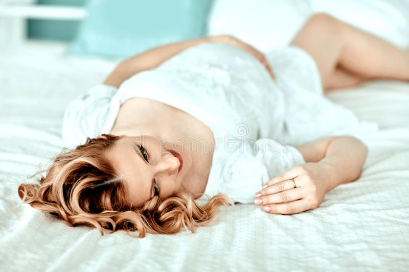 Close up.happy young pregnant woman lying on bed stock photography