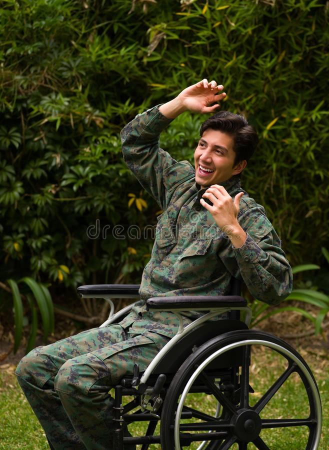 Close up of a happy young soldier sitting on wheel chair at outdoors in the patio, in a backyard background.  royalty free stock images