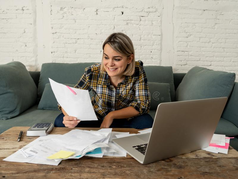 Close up of happy young woman sitting on the sofa surrounded by papers calculating and paying bills. Happy attractive entrepreneur or housewife woman calculating royalty free stock photos