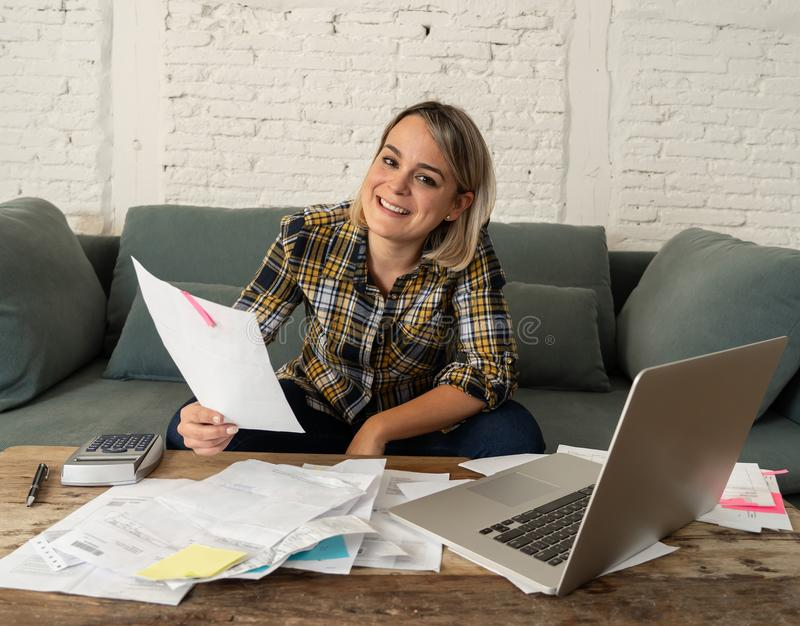 Close up of happy young woman sitting on the sofa surrounded by papers calculating and paying bills. Happy attractive entrepreneur or housewife woman calculating royalty free stock image