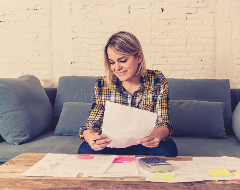 Close up of happy young woman sitting on the sofa surrounded by papers calculating and paying bills. Happy attractive housewife or entrepreneur woman paying stock images