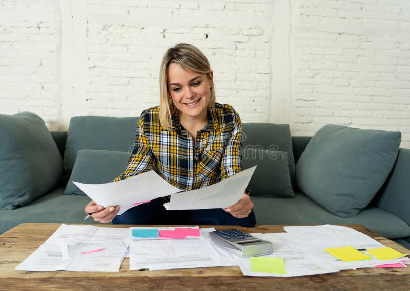 Close up of happy young woman sitting on the sofa surrounded by papers calculating and paying bills. Happy attractive housewife or entrepreneur woman paying stock photo