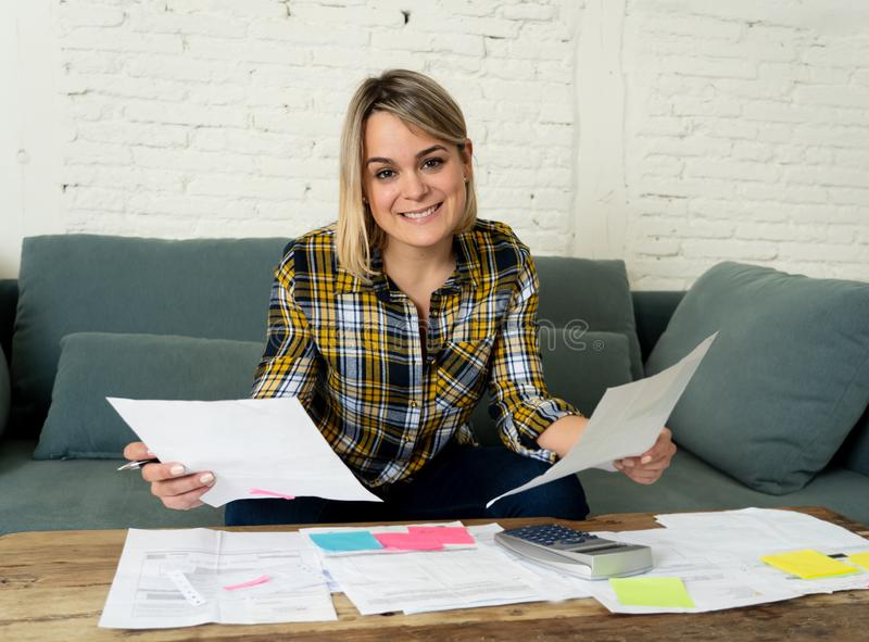 Close up of happy young woman sitting on the sofa surrounded by papers calculating and paying bills. Happy attractive housewife or entrepreneur woman paying stock photos