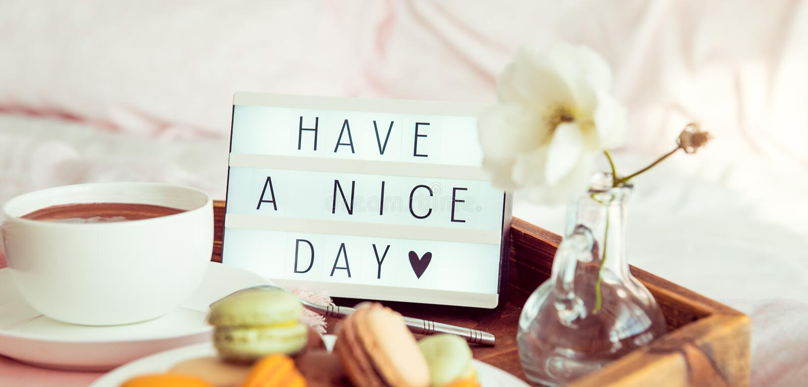 Close up Have a nice day text on lighted box on the tray with breakfast in bed. Cup of coffee, macaroons, flower in vase. Good. Morning mood. Hospitality, care stock photo