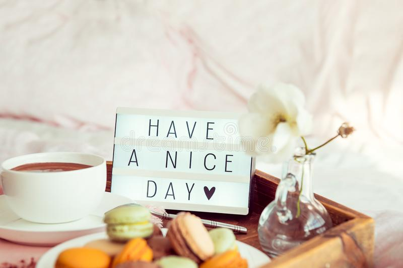 Close up Have a nice day text on lighted box on the wooden tray with breakfast in bed. Cup of coffee, macaroons, flower in vase. Good morning mood. Hospitality royalty free stock photos