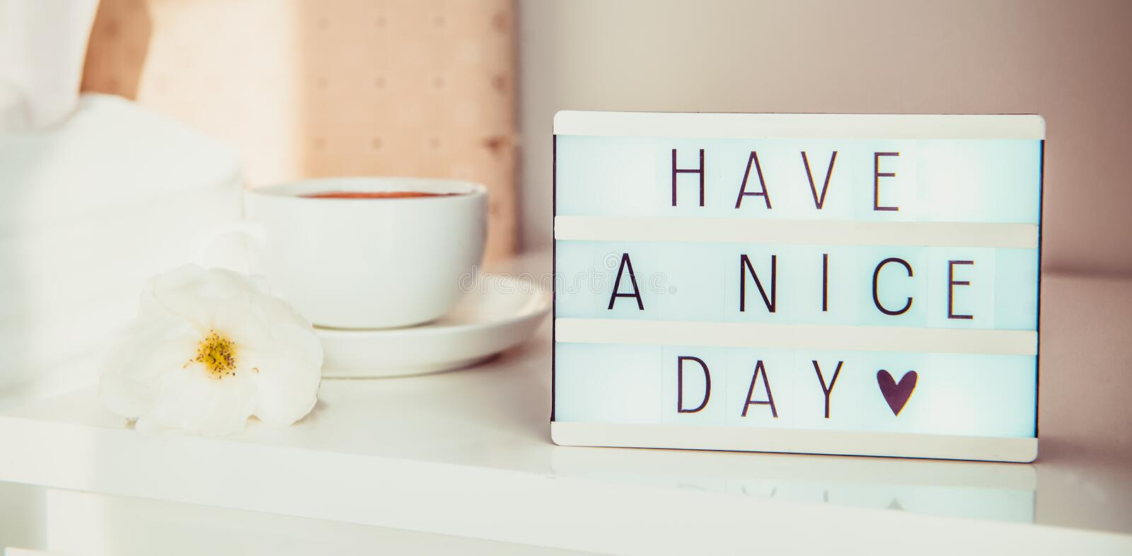 Close up Have a nice day text message on lighted box, cup of coffee and white flower on the bedside table in sun light. Good. Morning mood. Hospitality, care royalty free stock photos