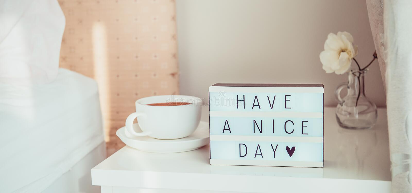 Close up Have a nice day text message on lighted box, cup of coffee and white flower on the bedside table in sun light. Good. Morning mood. Hospitality, care stock images