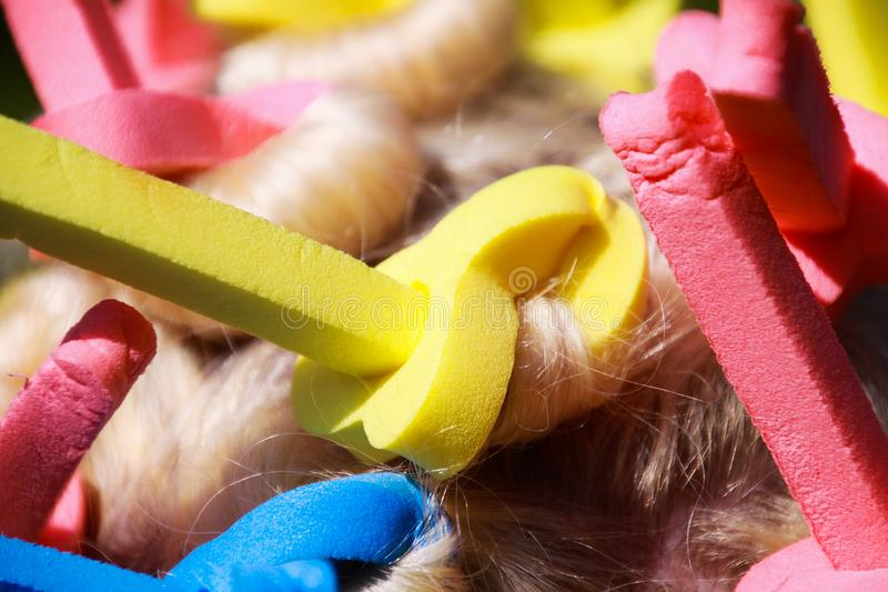 Close up of head of european woman with blonde hair and colorful old-fashioned foam curlers stock images