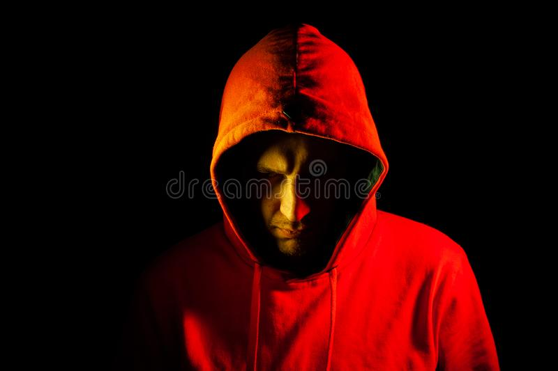 Close-up of the head of a man in an orange hood on the side of the side and looking down with a yellow backlight. Feeling before stock image