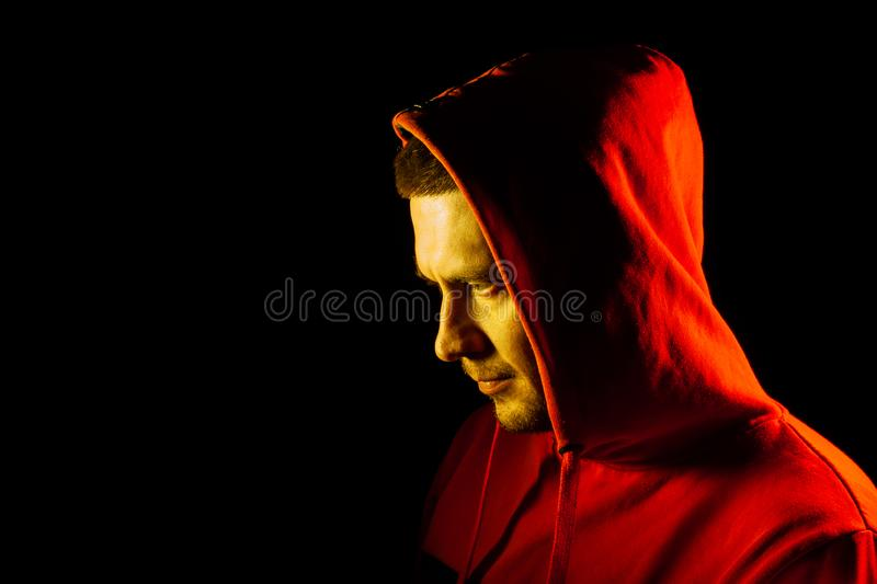 Close-up of the head of a man in an orange hood on the side of the side and looking down with a yellow backlight. Feelings before royalty free stock photo
